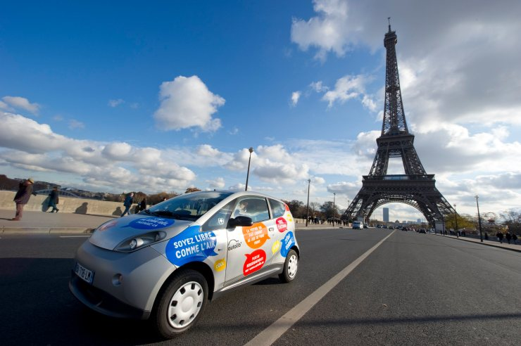 A Paris Autolib' electric car drives next to the Eiffel tower during a presentation ride in Paris
